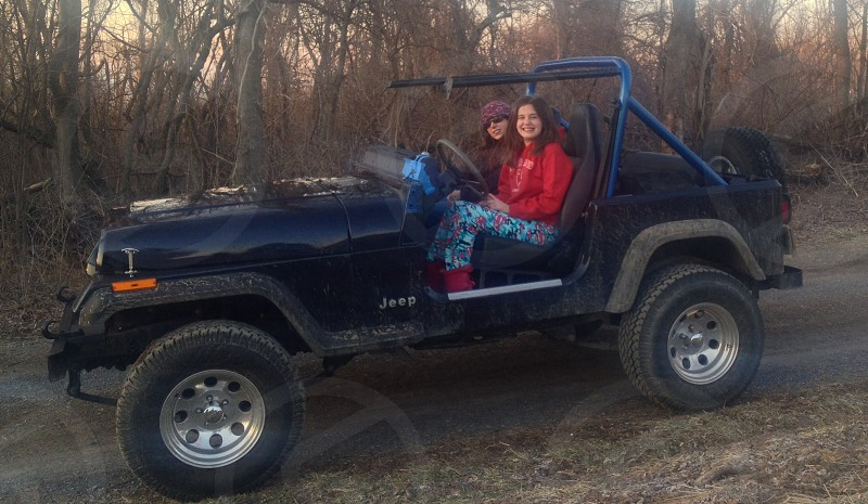 two seated smiling brunette girls sitting in  a black jeep photo
