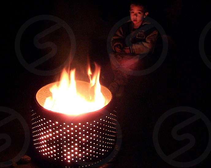 A little boy sits in the glow of a campfire photo