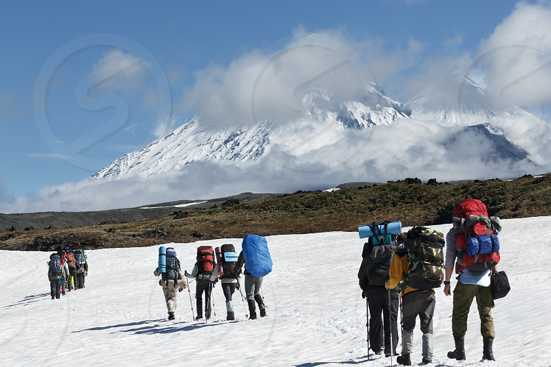 Hiking on the Kamchatka: a group of tourists is on the snowfield on a beautiful background of Klyuchevskaya group of volcanoes on a sunny day. Russian Federation Far East Kamchatka Peninsula. photo
