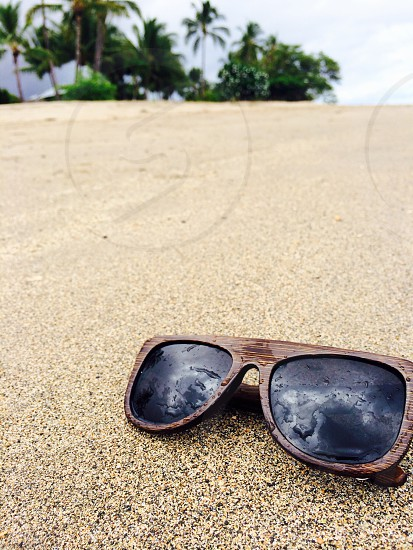 brown framed sunglasses on brown surface photo