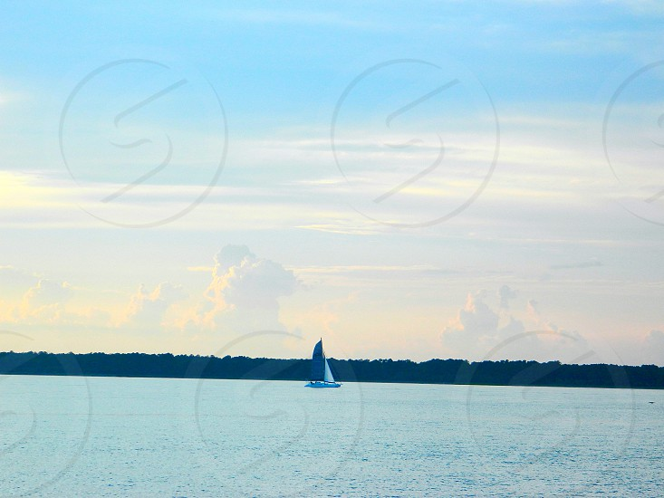 A single sailboat against the clouds at dusk in South Carolina photo