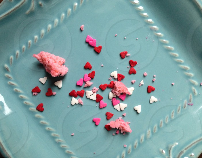 Crumbs from pink valentines donut. Heart sprinkles photo