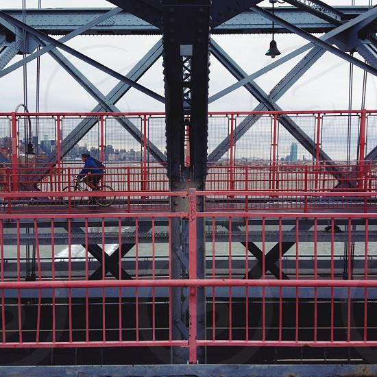 man bicycling on bridge photo