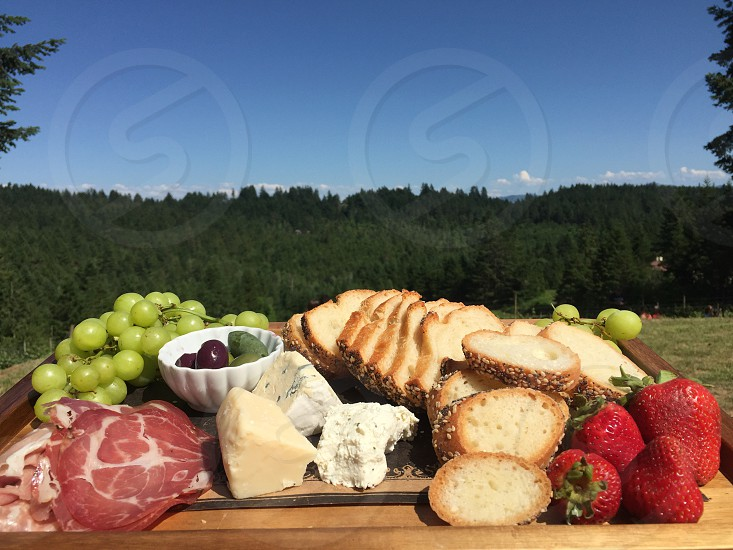 Cheese board breadsolives grapes cure meat cheeses strawberries  photo