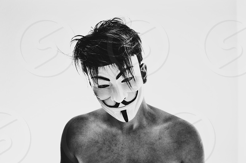 topless man wearing guy fawkes mask photo