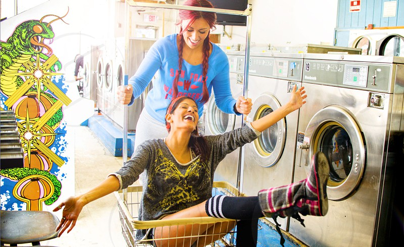 woman sitting in shopping cart and another woman pushing cart photo