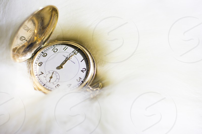 Old golden pocket watch on white fur photo