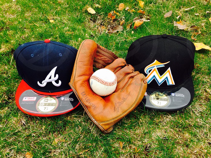 2 fitted caps and brown leather baseball gloves with baseball on it photo
