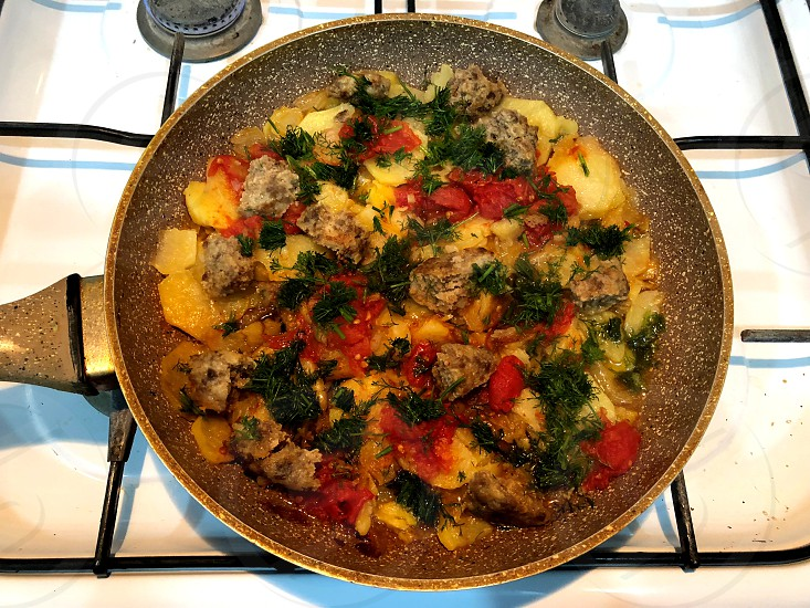 Lunch on a fast hand of the bachelor. Meat potatoes tomato herbs onions and other vitamins in a skillet.  photo