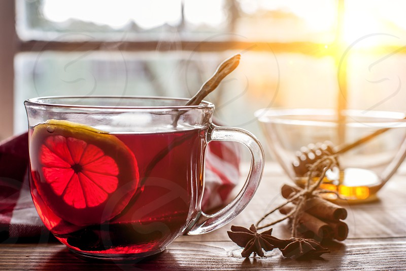 Tea with lemon on table with windows and sun in back photo