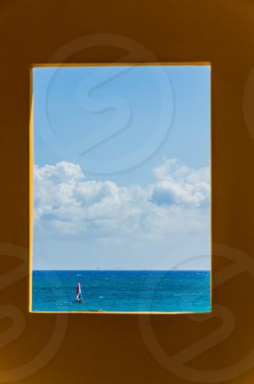 Image of sailboat on ocean shot through building photo