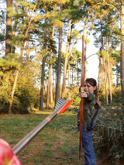 Bow arrow hunter girl shoot outdoors outdoorsman hunting aim apple trees sport strong child learn photo