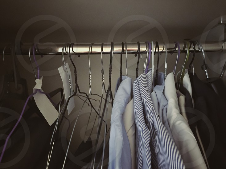 interior of a wardrobe with various shirts hung with hangers photo