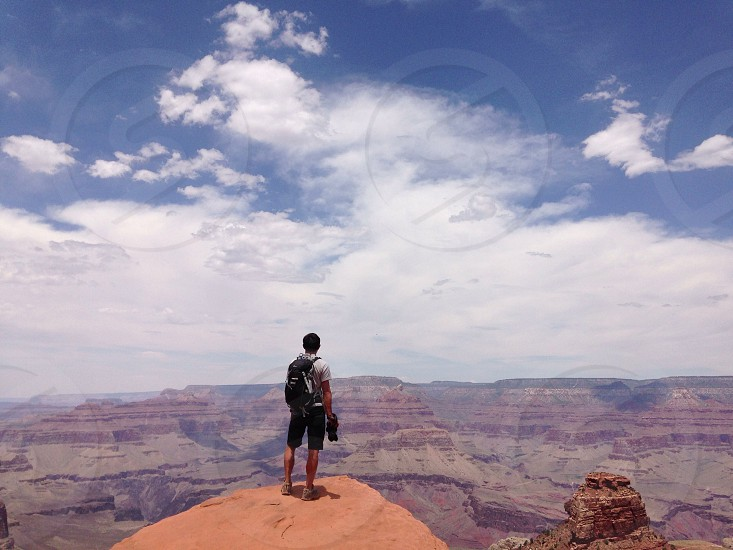 man standing on top of canyon photo