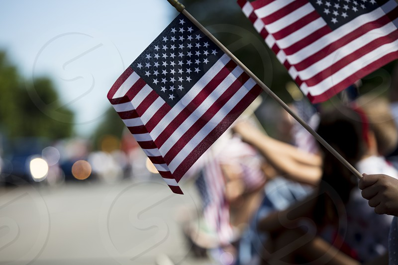 Flags waving at a fourth of July parade photo