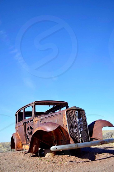 brown classic passenger vehicle body frame on the sand photo