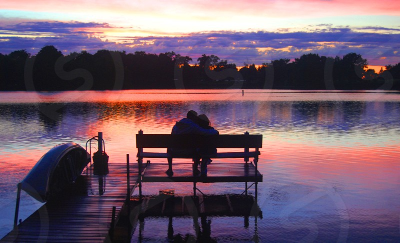 Couple on a Dock by the Lake at Sunset photo
