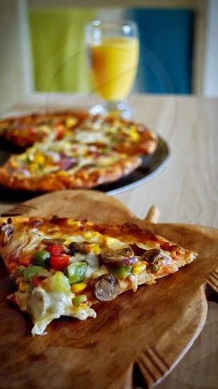 cheese pizza on brown wooden plate in tilt shift lens photography photo