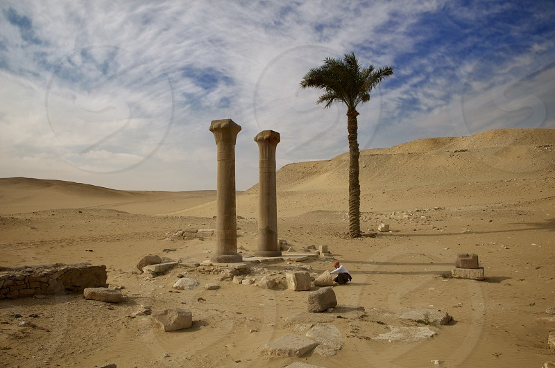 The entry point to the Saqarra plateau near Cairo Egypt. palm desert columns ruins sand rocks blocks archeology sky clouds drama dramatic photo
