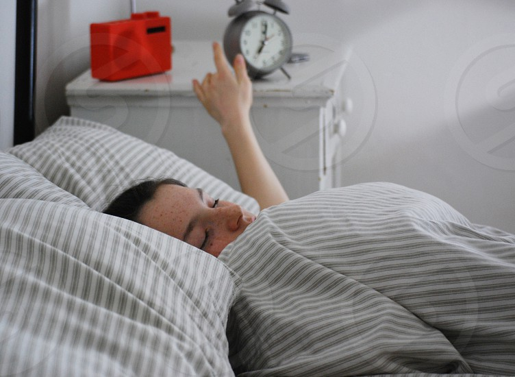 Woman reaching for the alarm in the morning. Snoozing in bed. photo