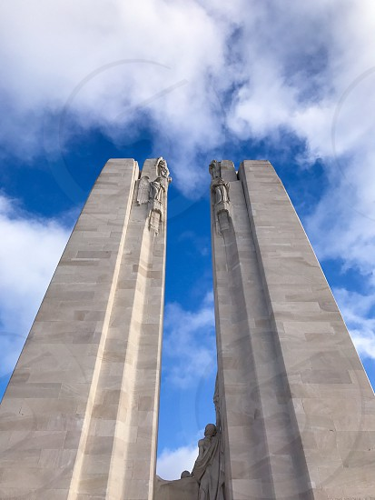 Outdoor day vertical portrait colour Vimy Ridge France Europe European Battle of Arras Western Front World War One WWI WW1 First World War battleground war warfare trench Trenches memorial remembrance commemoration white marble stone carved Canada Canadian mourning monument sky clouds blue photo
