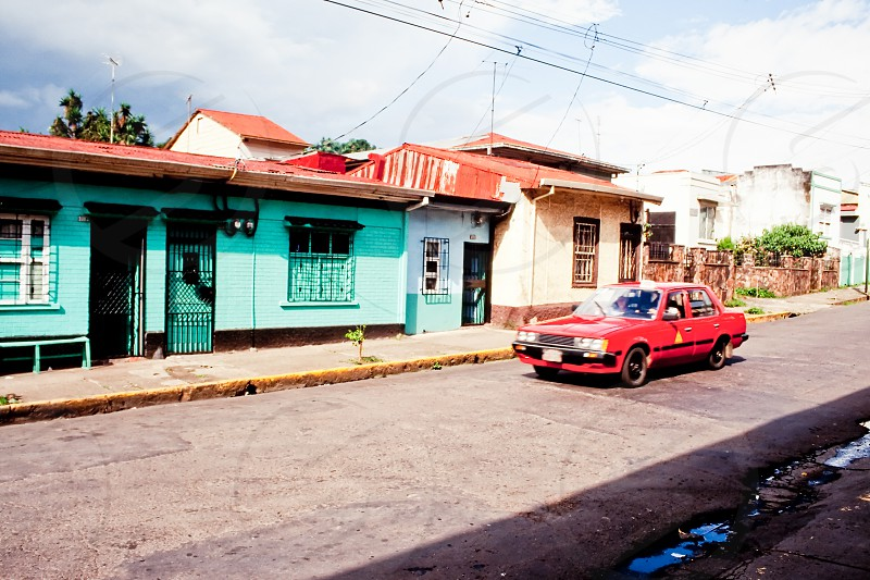 Red taxi cab car driving on street in San Jose capital of Costa Rica in front of small colorful houses photo