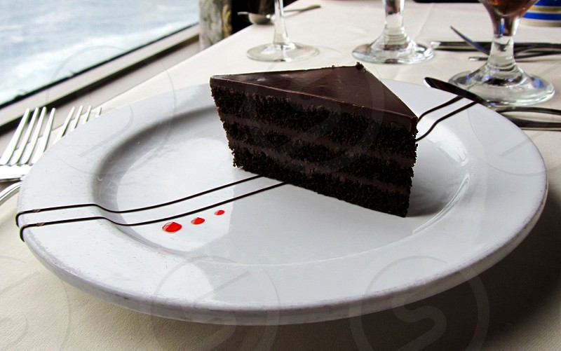 Fancy chocolate cake on white plate overlooking water photo