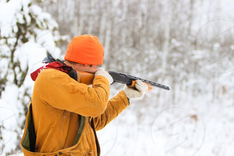 hunt hunter hunting recreate recreating hobby outdoors outside gun firearm shotgun aim point orange safety game coat white snow woods forest photo