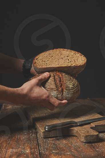 Men's hands hold two halves of rye bread on a dark background photo