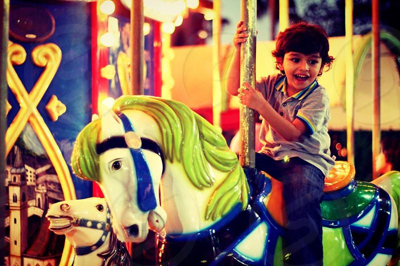 Childhood joy happiness fair theme park son horse excitement colors carousel  photo