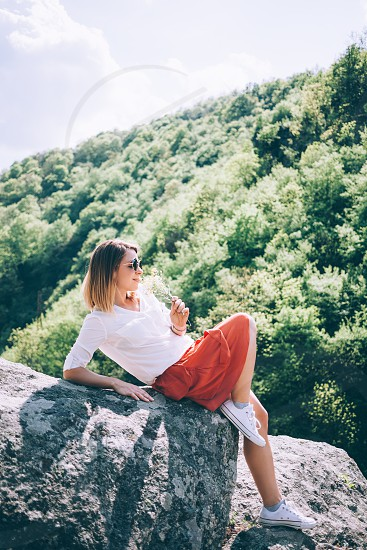 Young woman sitting on the rock in nature with flowers in her hands photo