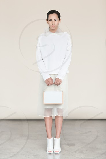 woman wearing white sweater and sheer skirt holding white bag wearing white peep toe ankle boots standing in front of white wall photo