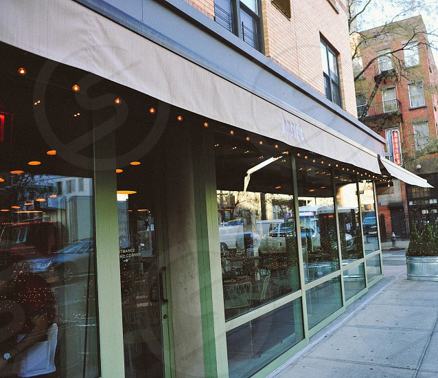 light strand under a brown awning over a glass window restaurant photo