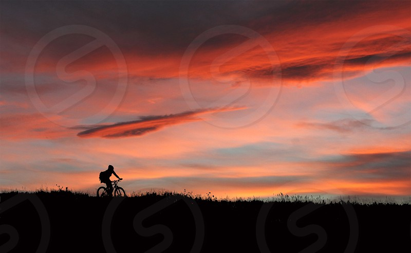 A bicyclist is silhouetted against a red sky in Colorado at sunset. photo