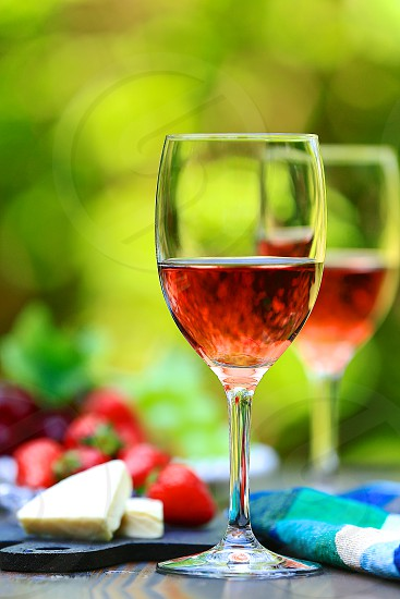 beverage bokeh bright cheese copy space drinks DSLR camera flatware fresh fruit grapes greenery background hero shot longitudinally long natural daylight no branding outdoor pink portrait rose wine Rosé Wines rustic wood surface rustic wood table strawberry Summer feeling Summer tone sun peeking through tablecloth trees background vertically long wine wine glasses photo