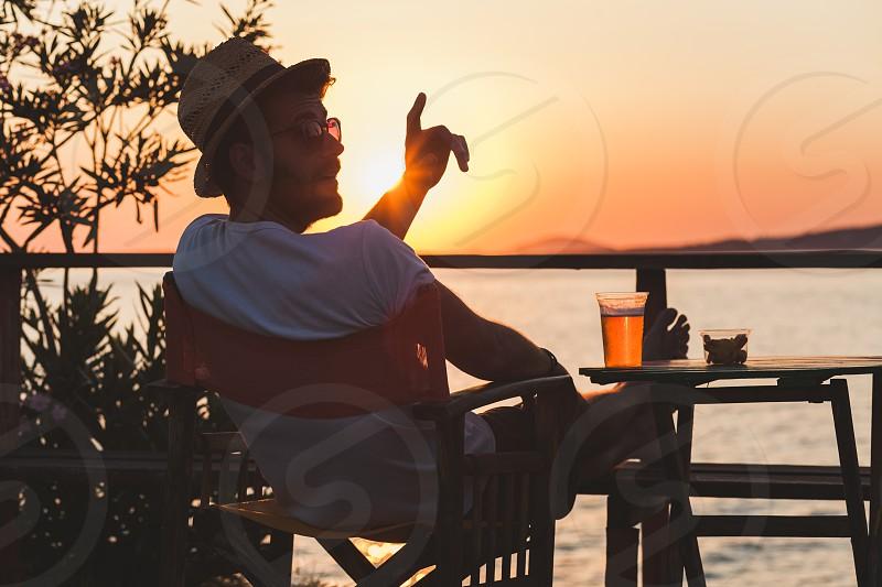 Young man enjoying sunset at a beach bar calling for waiter photo