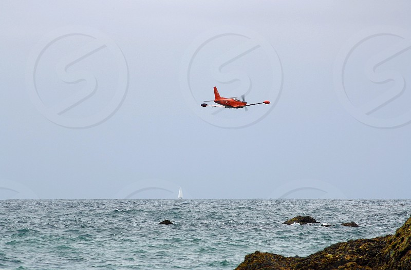Red seaplane flies neat the rocky shore of the ocean photo