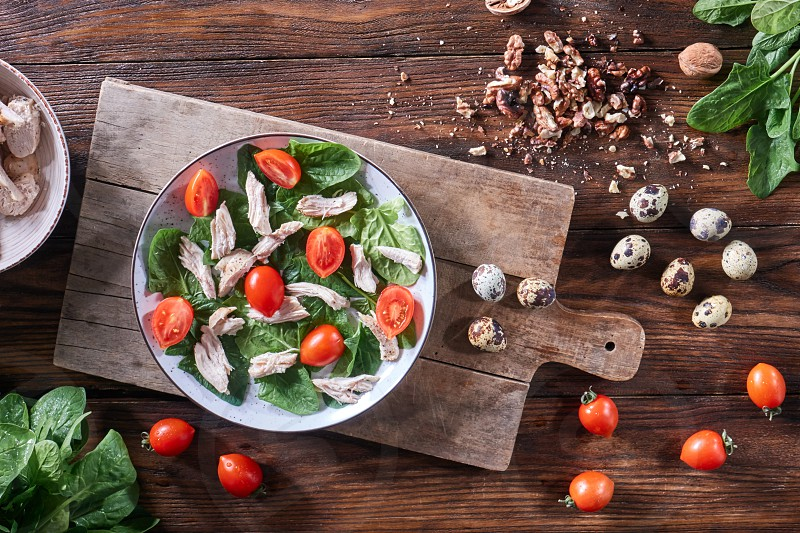 Healthy freshly prepared salad of quail eggs meat tomatoes and spinach in a plate on a wooden board on the kitchen table. Dietary lunch. Flat lay photo