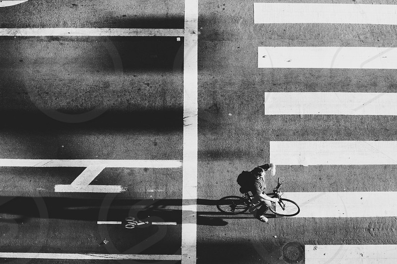 grayscale photography of person using bicycle photo