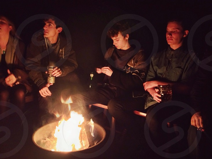 4 people sitting infront of a bonfire photo