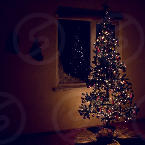A dark serene night Christmas scene with a Christmas tree lights and a window. photo