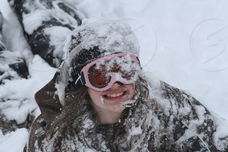 girl covered in snow wearing ski goggles photo