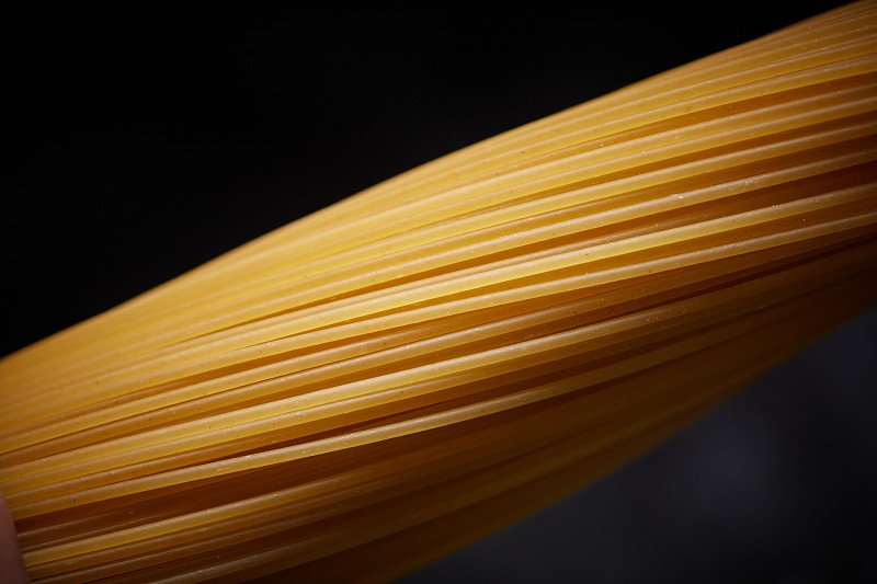 Macro photo of a yellow long Italian spaghetti on a black background. photo