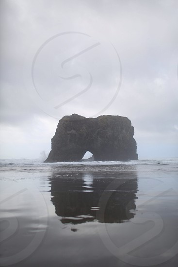 black rock formation on water photo