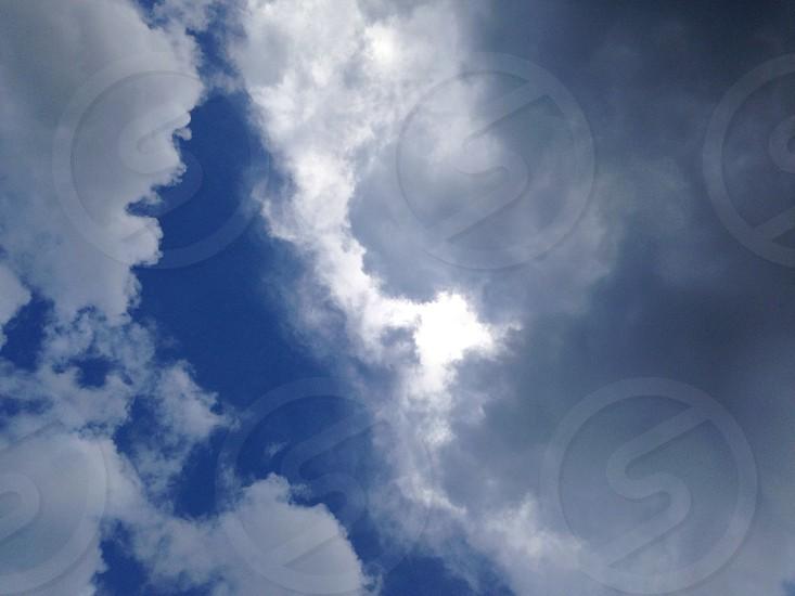 sun shining through gray clouds in a blue sky photo