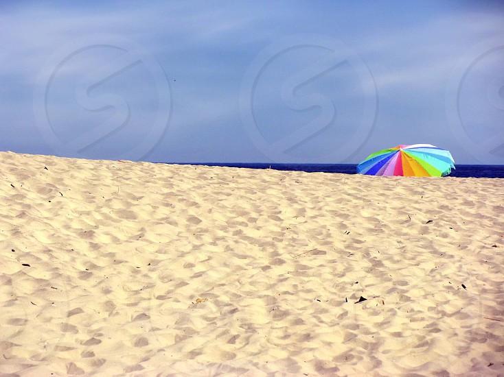 beach multicolored umbrella on seashore with blue sky  photo