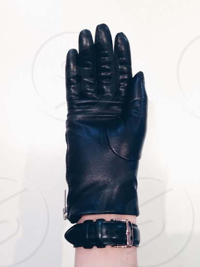 black leather hand gloves and black strap watch photo