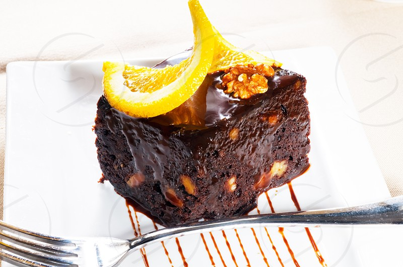 fresh baked delicious chocolate and walnuts cake with slice of orance on top photo