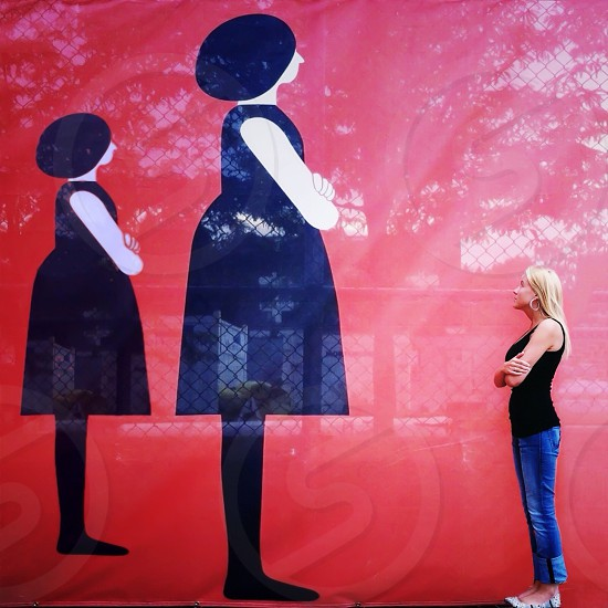 woman in black tank top standing in front of wall art photo