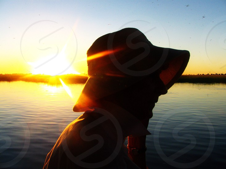 silhouette photography of person wearing hat near body of water photo